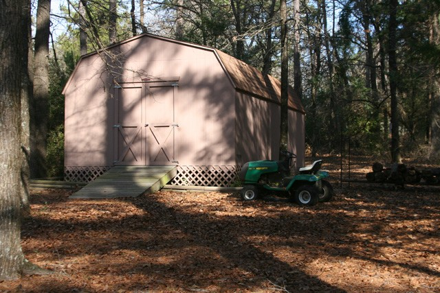 very large storage shed somewhat hidden in the woods.